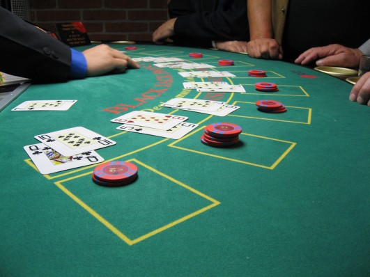 """Blackjack board"". Licensed under Public Domain via Wikimedia Commons - https://commons.wikimedia.org/wiki/File:Blackjack_board.JPG#/media/File:Blackjack_board.JPG"