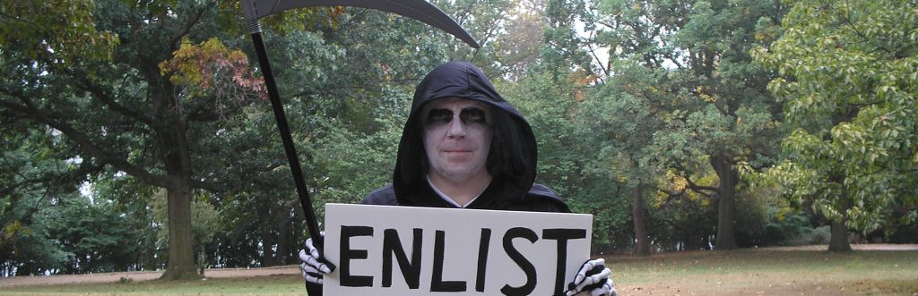 "Photographer, Activist Thomas Good in costume - ""recruiting"" for the military as the Grim Reaper, October 2007. The photograph was taken by the subject's 14-year-old son, Nathaniel Good. In March of 2007 the photo was reprinted as the cover shot on ""Peacework"" magazine, a publication of the American Friends Service Committee."
